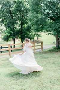 A woman in a white wedding dress twirls, holding her skirt. She stands on a lawn by a tree. Behind her is a tall wooden fence
