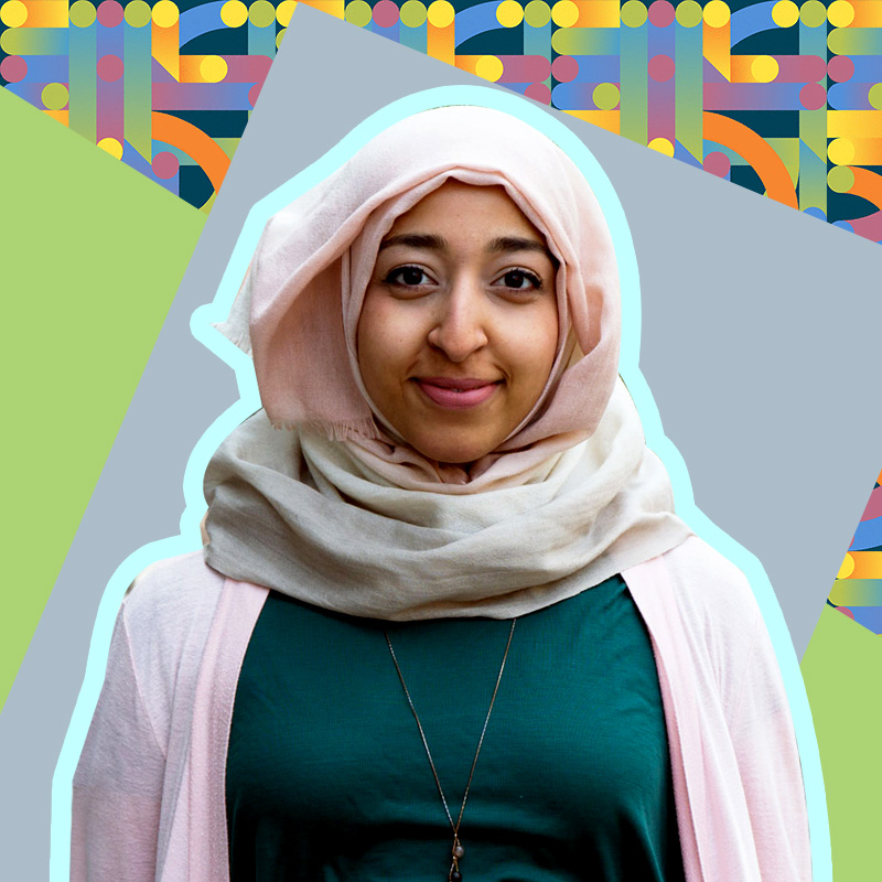 A photo of Huda Idrees smiling wearing a muted pink hijab and a green top. Via HudaIdrees.com