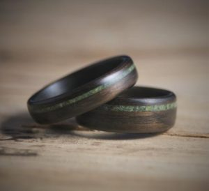 Two rings made from dark wood with a green stripe running across them
