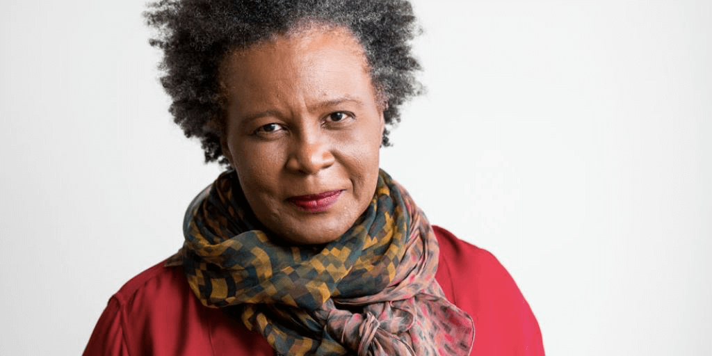 A photo of Claudia Rankine, a woman of color with graying hair, wearing a multi-colored scarf and a red sweater