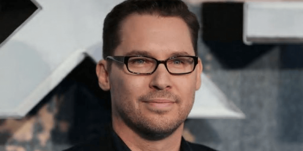 [image description: a close-up on Bryan Singer's face. He is a white man with green eyes wearing rectangular black glasses. He has short dark hair.] via cbc.ca