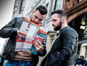 Two men in leather jackets pore over a London map