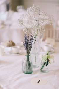 Dried lavender, baby's breath flowers, and roses each placed in glass jars on a white tabelcloth, next to a piece of paper that has the number one on it