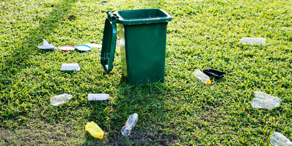 A green recycling container on a green lawn is open with trash spread on the ground around it.