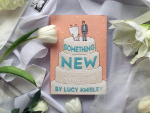 A photo of the book Something New: Tales From a Makeshift Bride by Lucy Kinsley laid out on a table with a white tablcloth on it, surrounded by white crepe paper, tulle, white flowers, and part of a photo booth picture of a couple making faces
