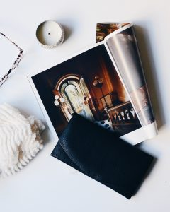 Photo from above of a candle, a pair of glasses, a magazine open to a page with a woman standing at a terrace window thrown open, a black leather clutch, and a white fluffy scarf laid out on a white surface