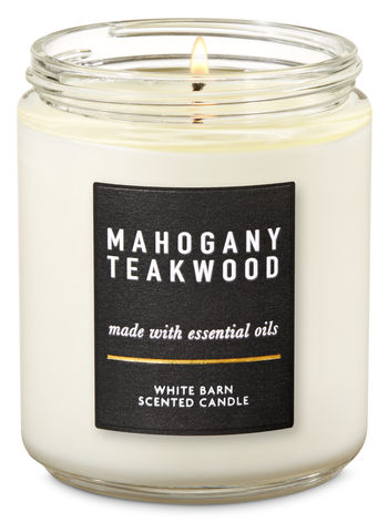 [Image Description: Lit one wick white candle in Mahogany Teakwood scent.] Photo via Bath and Body Works