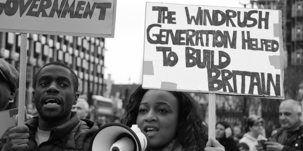 A black and white photo of a protest. A woman is holding up a white megaphone and a sign that says 'The Windrush Generation Helped to Build Britain'. A man is standing next to her and also holding a sign