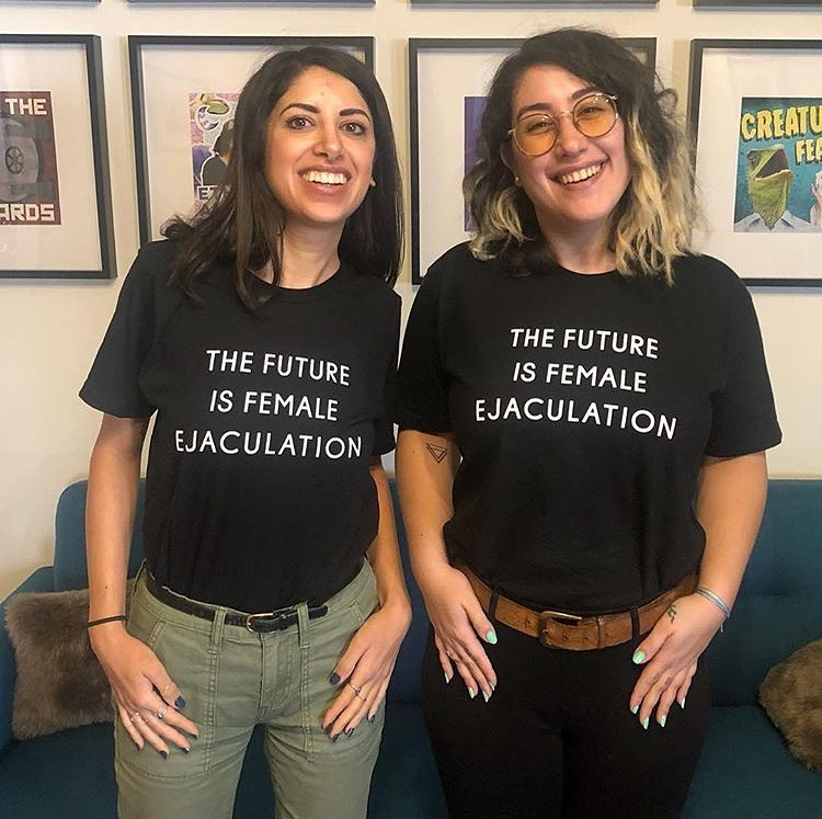 "Two smiling women wearing black T-shirts that read ""the future is female ejaculation"""