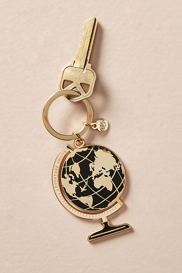 """[Image Description: Gold and black keychain of the world globe with the words """"Adventure Awaits"""" written in the outline of the globe. A golden key is attached to the keychain.] Photo via Anthropologie"""