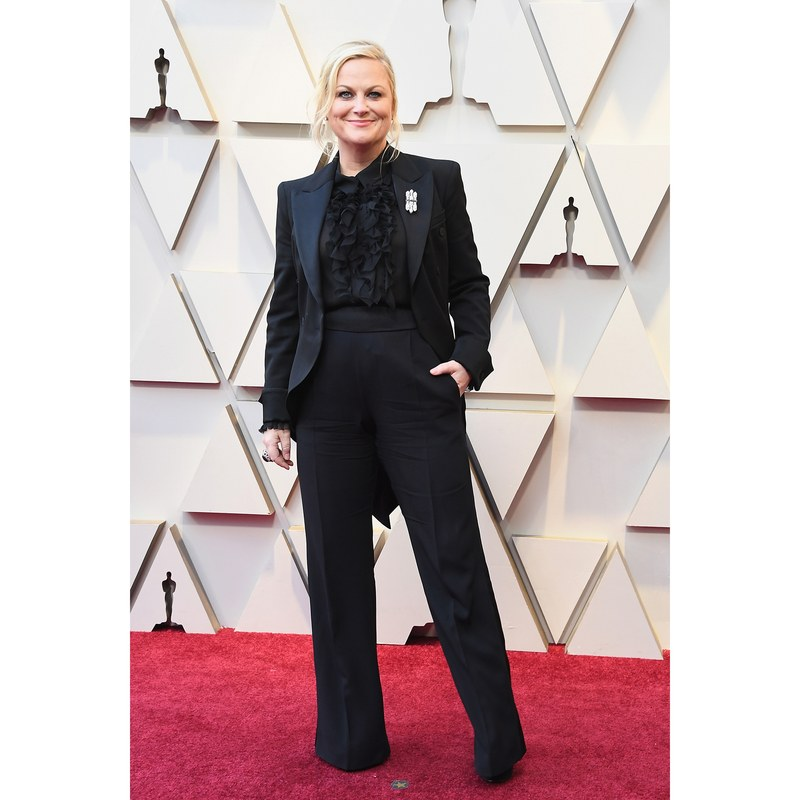 [image description: Amy Poehler, a blonde white woman, stands on the Oscars red carpet. Left hand in her pocket. She is wearing a black tux] via Getty Images.