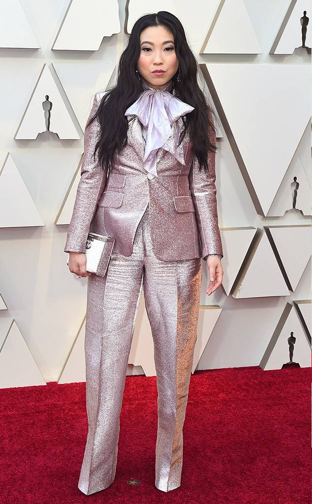 [image description: An East Asian woman with long dark hair in a pink simmering tuxedo and a pussy bow poses on the Red Carpet] via eonline.