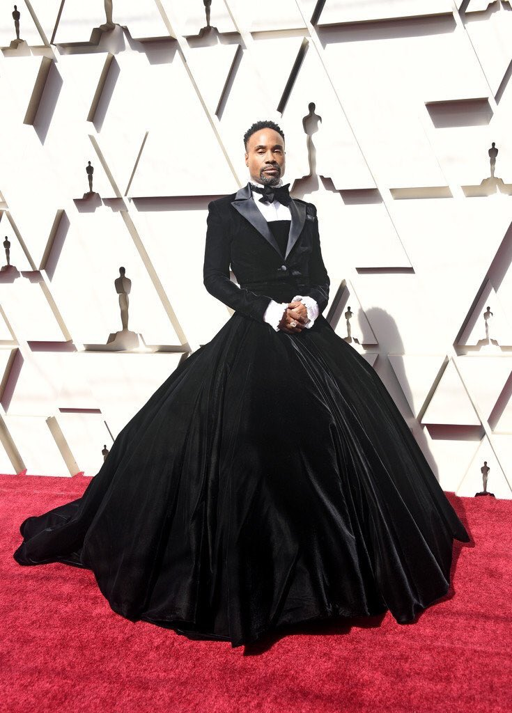 [image description: Billy Porter, a tall black man, poses on the Oscars red carpet in a black tuxedo gown. His hands are folded and he is staring directly into the camera] via Getty Images.