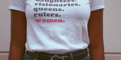 "Close-up of a woman's white T-shirt. Shirt reads ""daughters. visionaries. queens. rulers. women."""