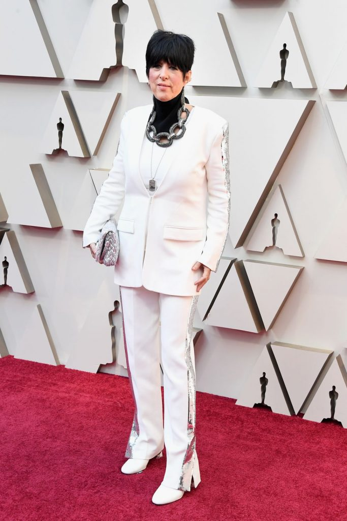 [image description: a white woman with short dark hair and a prominent necklace in a white suit on the Red Carpet] via Steve Granitz/Getty Images.