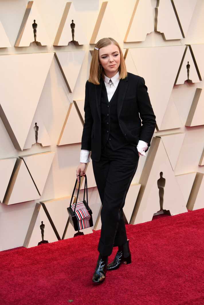 [image description: A blonde white woman in a three piece black tux strolls on the Red Carpet with a bag in hand] via stylecaster.