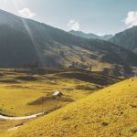Landscape nature photo of valley lands and mountains in Kashmir. Photo of scenery is taken during the afternoon with the hills and land ranging in yellow to green colors.