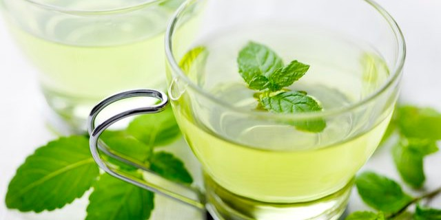 An aesthetic setting with peppermint leaves arranged around a glass cup of peppermint tea. There is a peppermint leaf placed in the tea.