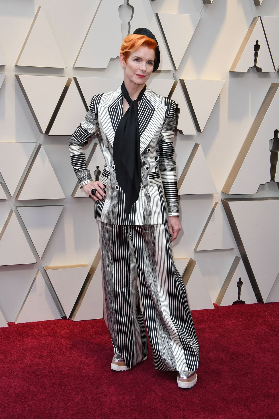 [image description: A blonde, white woman in a black and white striped suit poses with a hand on her hip on the Red Carpet] via Getty Images.