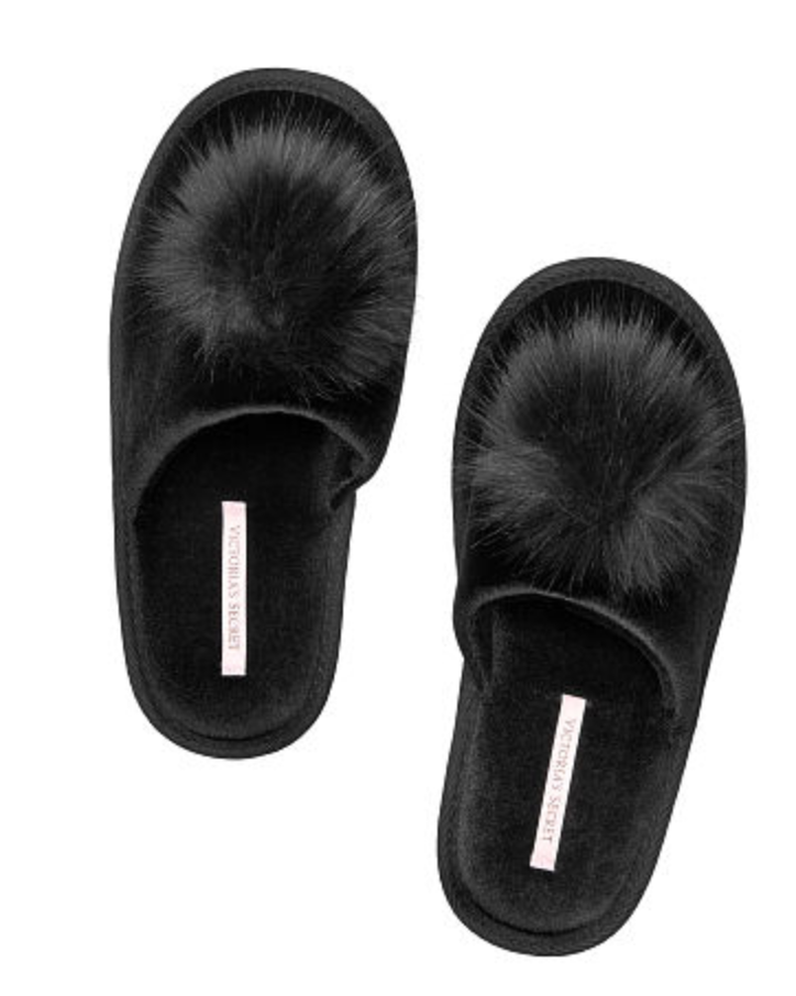[Image Description: Black fuzzy open back slippers with a big black pom pom  at the front of the shoe.] Photo via Victoria's Secret