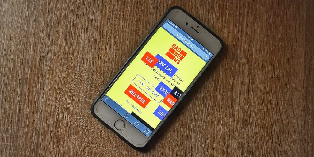 A white iPhone in a black case lies atop a light brown wooden desk. On the screen is the cover image of the fake news game, Bad News, which features a yellow background and the following words: LIE, CONCEAL, and WHISPER.