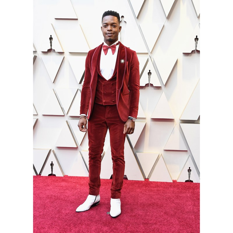 [image description: Stephan James, a tall black man, on the Oscars red carpet in a velvet red three-piece suit with a red bow tie and white boots] via Getty Images/Allure.