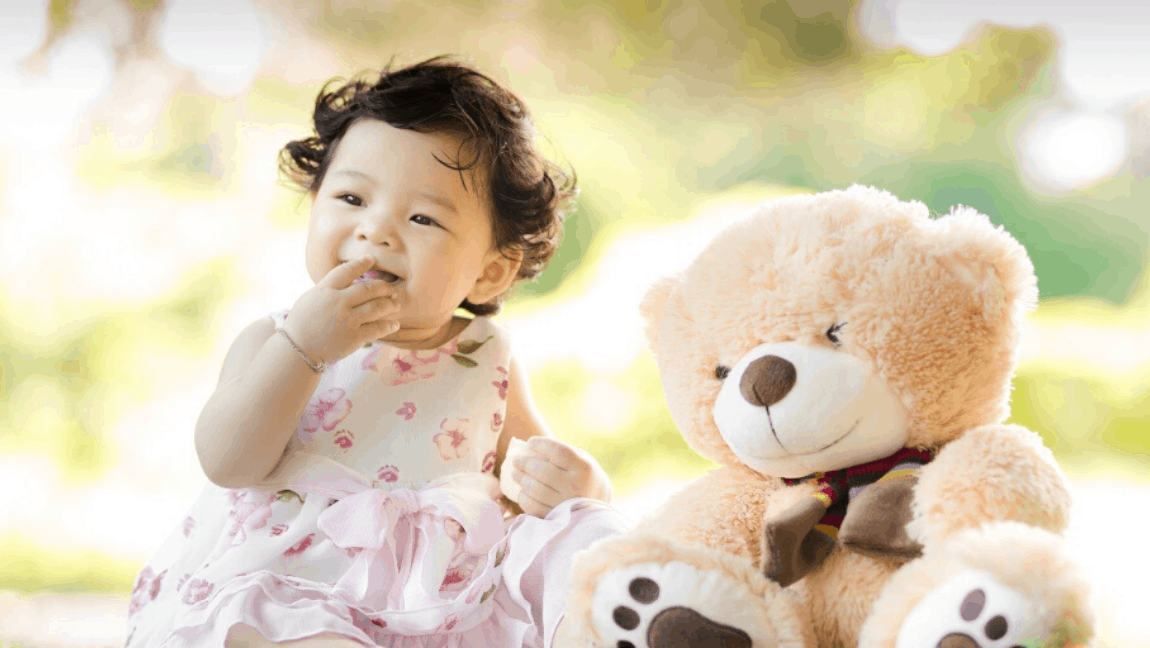 [Image description: A toddler in a pink-and-white floral dress is sitting outside in the sun. To her left is a light brown teddy bear.] Via Singkham on Pexels