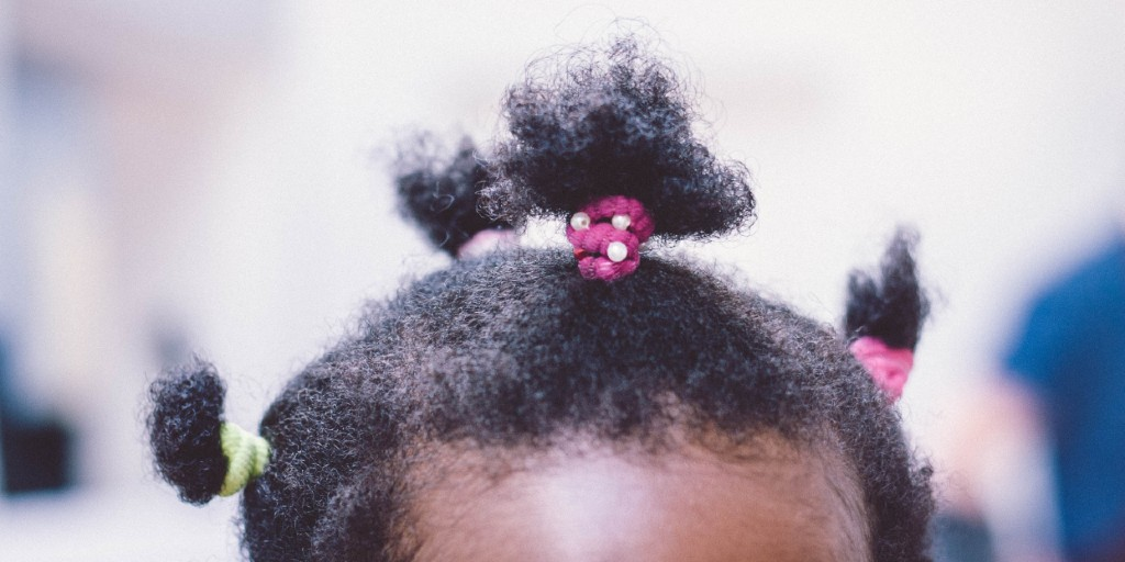 The top of a young African American girl's head. Her hair is styled in small pony tails.