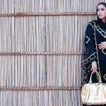 A woman wearing a hijab and carrying a gold purse, wearing all black.