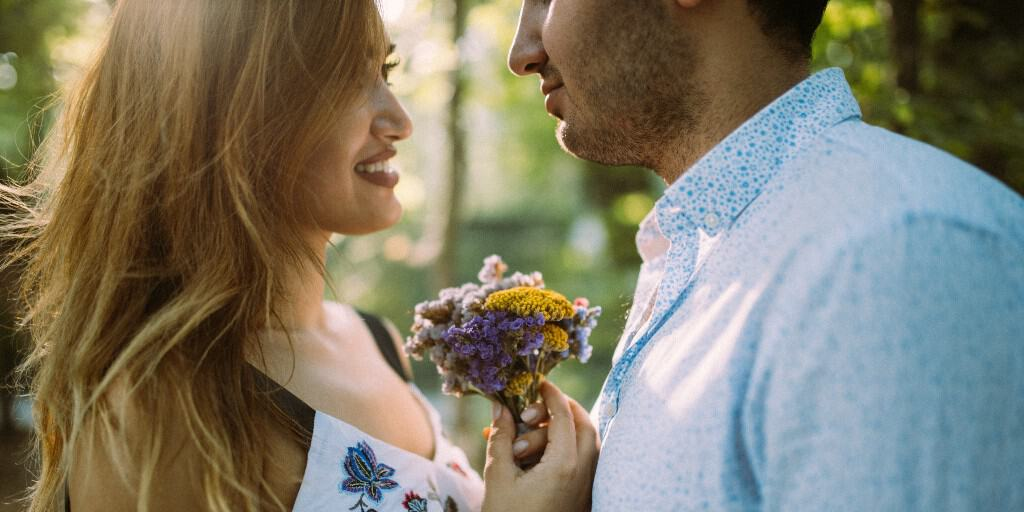 [Image description: A woman with brown hair wearing a sundress looks at a man wearing a blue shirt. They stare at each other lovingly holding flowers between them.] via Alvin Mahmudov on Unsplash