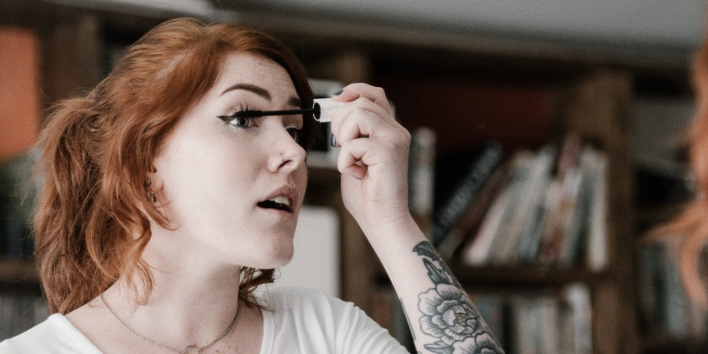 A woman leaning forward and applying mascara to her eyelashes.
