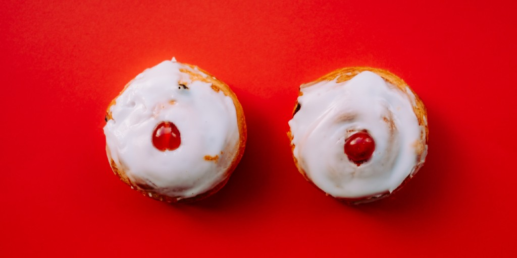 Two cupcakes covered in white icing with a cherry on top of each sit side-by-side on a bright red surface.