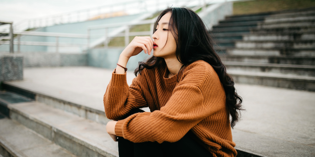 Young Asian woman with long hair deep in thought sitting on the stairs wearing a burnt orange colored knit sweater and black pants.