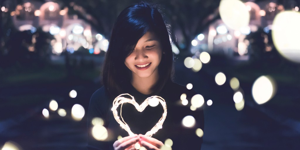 Asian girl smiling down on lighted strings she is holding that are shaped into a heart. The background is dark with several balls of light floating around the girl.