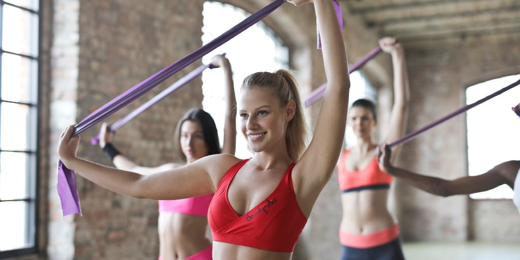 Group of four smiling women wearing sports bras and yoga pants at a fitness studio doing pilates with purple resistance bands.