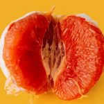 A bright orange peeled pomelo fruit rests on a canary yellow surface. A few wedges are taken out of the fruit so we see the centre.