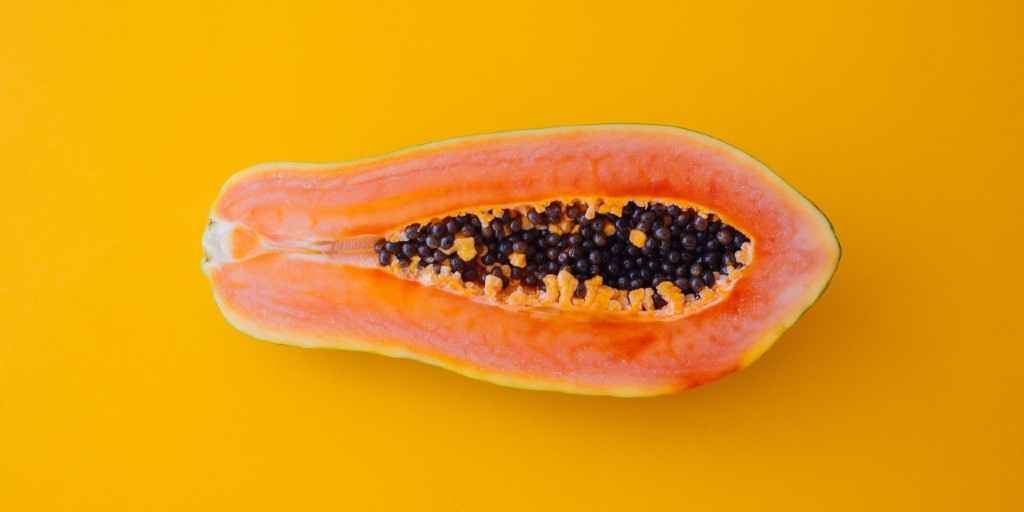 A papaya cut in half length-wise and with its seeds still inside lies horizontally on an orange surface.