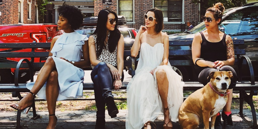 Four women of different ethnicities are sitting on a bench. A couple of the women are talking while others looking in different directions.