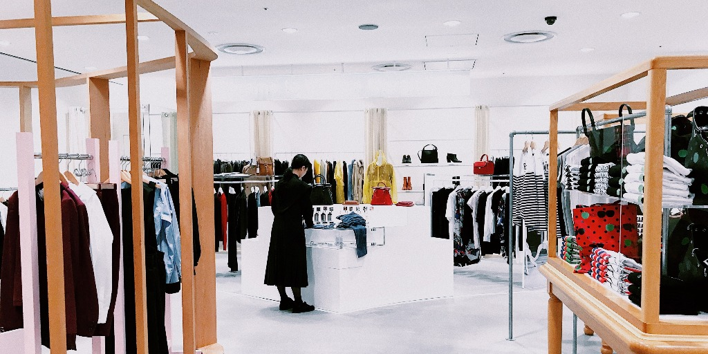 A sparse clothing store with white finishes and a customer wearing a black outfit.