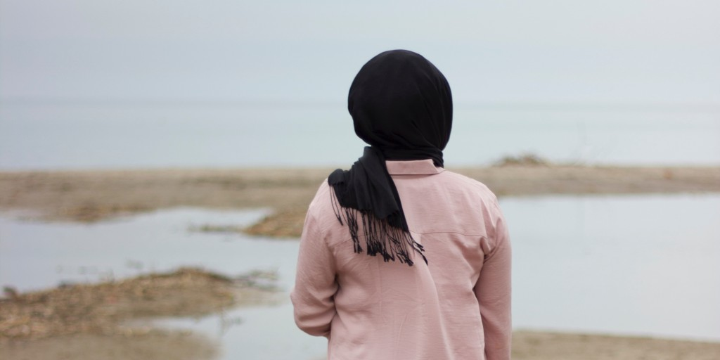 A woman in a black headscarf and a pink jacket has her back to the camera, facing a beach