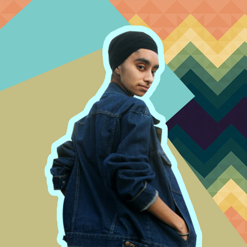 Jasmin Kaur is looking back at the camera and is wearing a black turban, and a baggy jean jacket with her hands in the pockets.