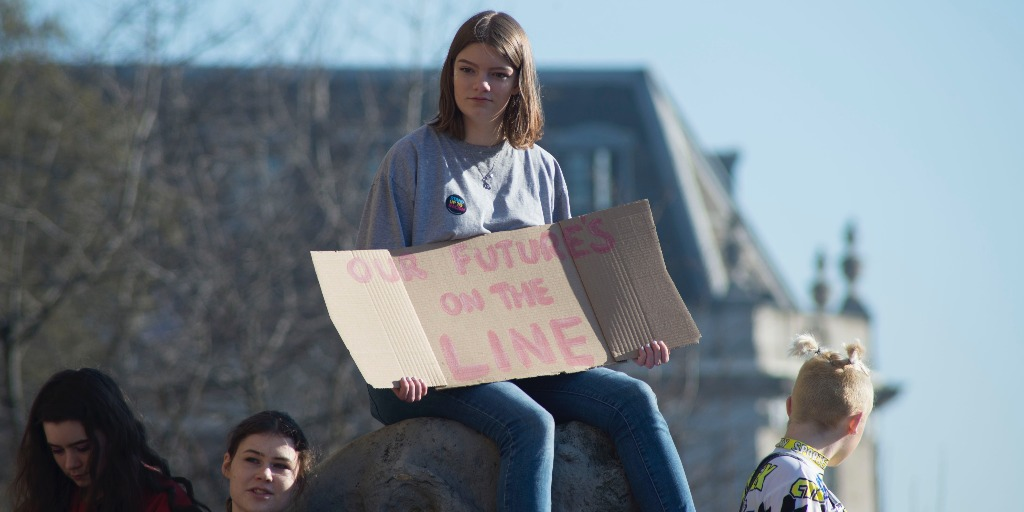 "[Image description: a woman holding a cardboard sign reading ""our future's on the line""]. Via Josh Barwick on Unsplash."