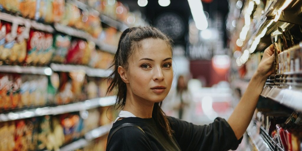 A woman in a shop isle holding a product and looking directly at the camer