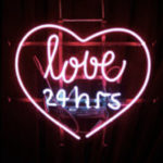 "A neon sign that says ""love, 24 hrs"" with a red neon heart around it."