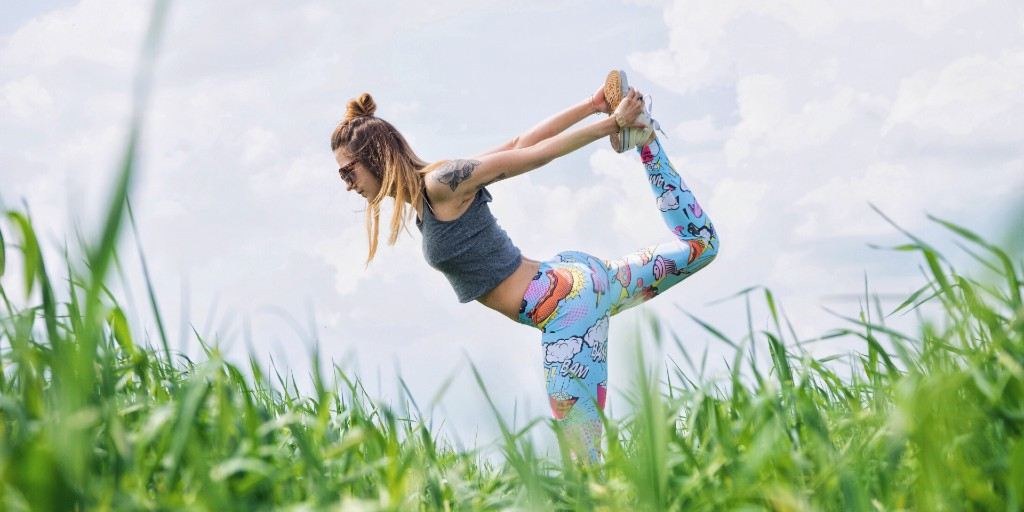 Woman pulling leg up from behind in a yoga pose in a grassy field.