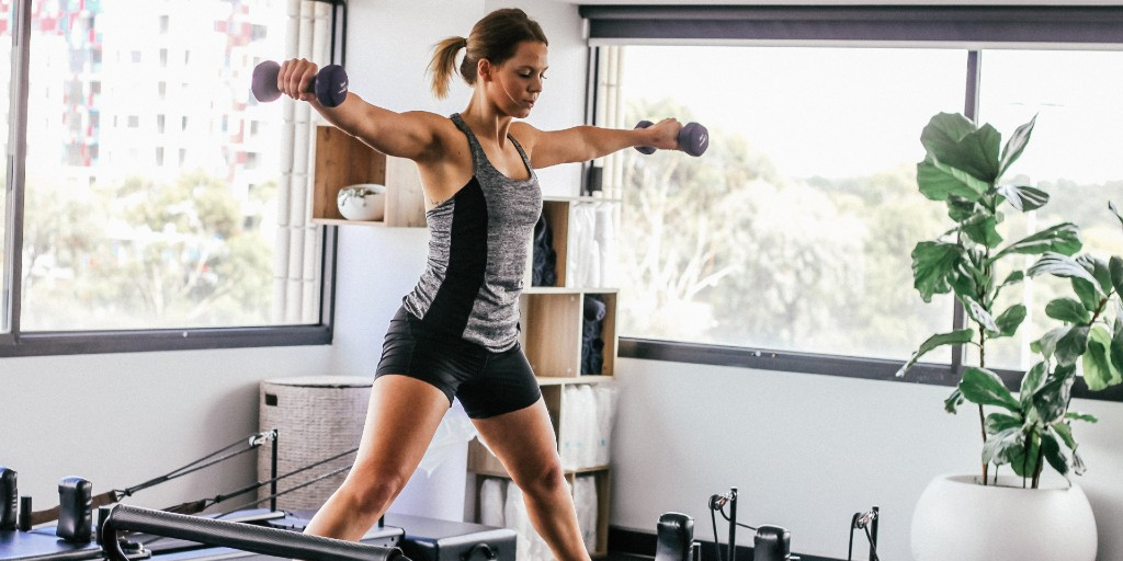 Woman holding dumbbells standing on a reformer in a Pilates studio.