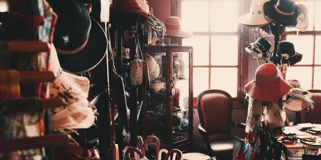 Interior of a room with an array of accessories including hats, scarves, and handbags.
