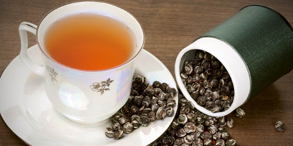 A white china cup of oolong tea on a matching white saucer. A green and white container full of rolled tea leaves are spilling out onto the table and the saucer.