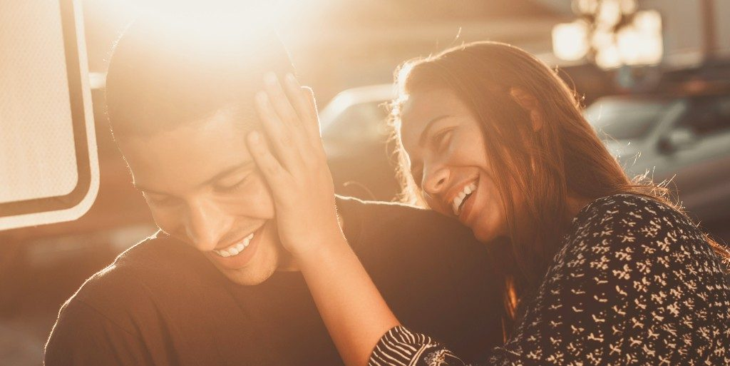 Man and woman laughing together in the sunlight. Woman is playfully pushing man's face away.