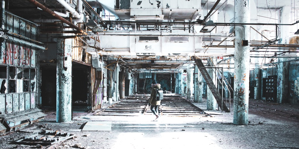 Someone wearing a winter coat, a black beanie and a backpack walks in an abandoned building.